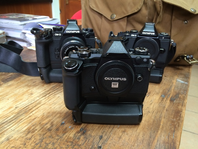 Olympus E-M5 Mark II all taped up for covert operations.  Behind is my original E-M5 and the E-M1.